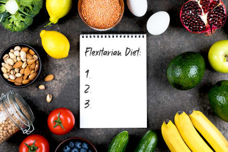 Photo for Flexitarian Diet Concept. Green vegetables, tomatoes, nuts, fruits, lentils, chickpeas, greens and empty notebook blank on grey concrete table. Flat lay, top view, copy space - Royalty Free Image
