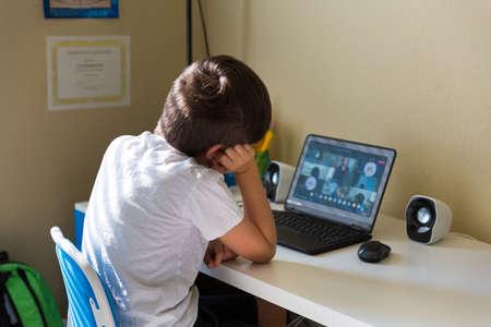 Foto de Boy student having a video call with his classmates in elementary school during covid-19 school shutdown - Imagen libre de derechos