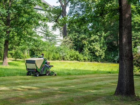 Photo pour Lawn tractor mows lawn in the park - image libre de droit