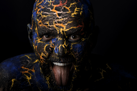 Photo for Conceptual Portrait of a brutal man painted in face art style over black background - Royalty Free Image