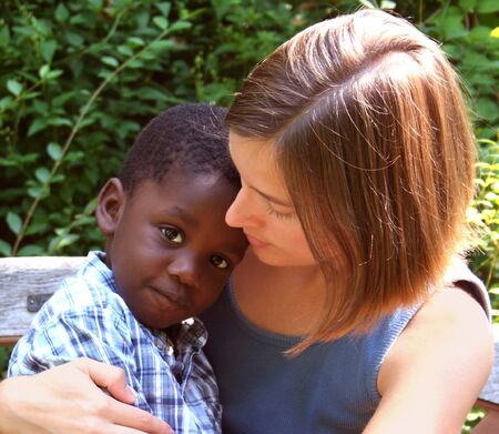 Young Caucasian woman with African American child - Diversity.