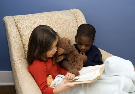 Two small children reading a story in a big, comfortable chair.  Diversity.