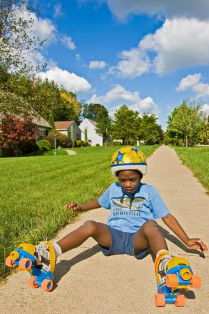 A young African American boy falls down while roller skating - wearing skates and a helmet.