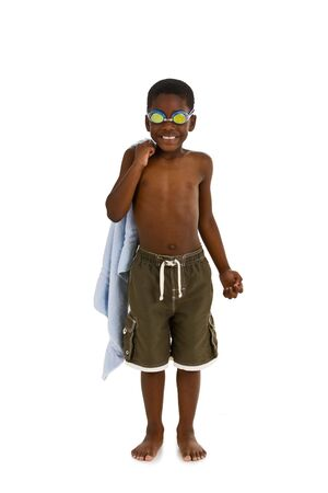 A young African American boy wearing swim trunks and goggles, and carrying a towel. Isolated on a white background.