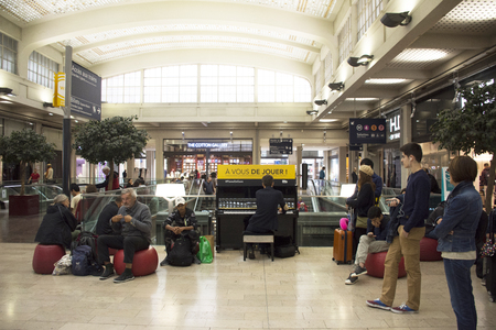 French man playing piano for show French people  and foreigner travlers at Gare de Paris-Est or Paris Gare de l'est railway station on September 7, 2017 in Paris, France