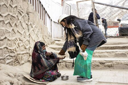 Photo for JAMMU KASHMIR, INDIA - MARCH 19 : Travelers thai women give money to old indian old woman beggar or untouchables caste sit and begging in market at Leh Ladakh on March 19, 2019 in Jammu Kashmir, India - Royalty Free Image