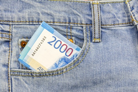 Russian banknotes in 2000 rubles inserted in the pocket of jeans