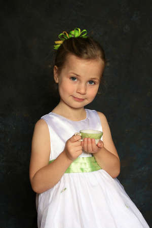 Cute little girl in a white dress holding a tea cup