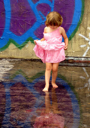 Photo pour Little girl playing in rain puddles with reflections - image libre de droit