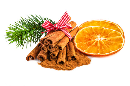 Orange slices with cinnamon and fir branch on white. Christmas rustic decoration on white background.
