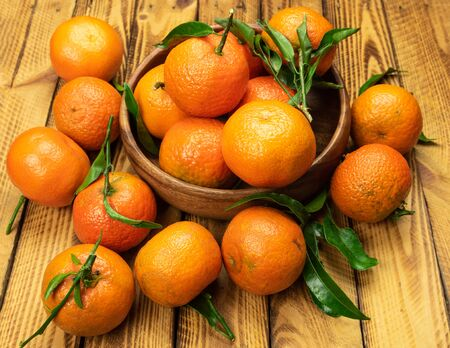 Photo for ripe organic mandarin fruits in wooden bowl over old wooden background - Royalty Free Image