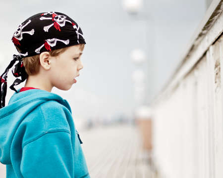 A rowdy young boy wearing bandanna standing on a pier