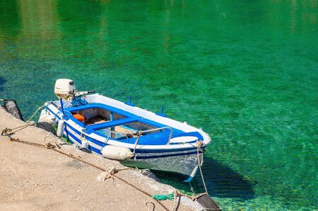 Small open deck motor boat in color of Greek flag moored in cosyport with clear water