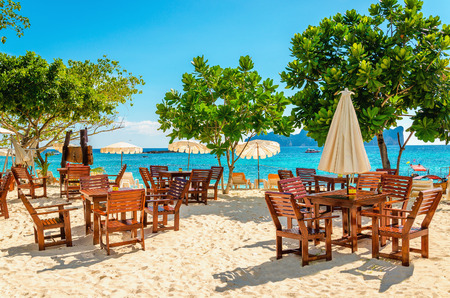 Wooden tables with sun umbrellas at a luxury resort close to an exotic beach