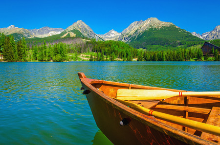 Wooden boat on a beautiful mountain lake in the background of the high peaks of mountains