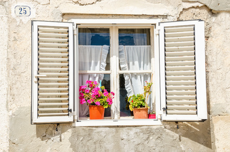 Picturesque window , shutters, colorful flowers against a white limestone wall