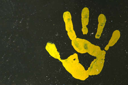 A yellow painted open hand print with five fingers on a black background of an old garbage drum