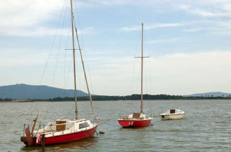 Sailing boats and motorboat moored on the lake