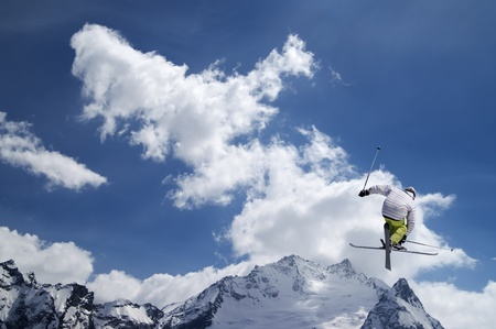 Freestyle ski jumper with crossed skis against snowy mountains
