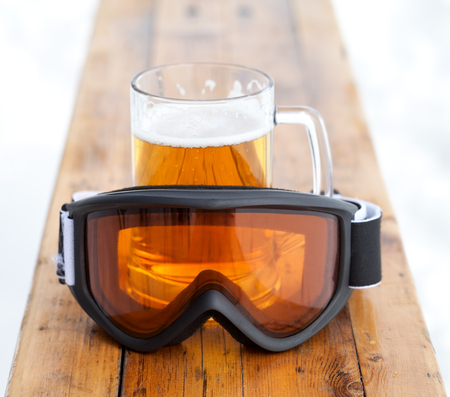 Ski goggles and glass mug with fresh cold beer on wooden bench in outdoor cafe at ski resort
