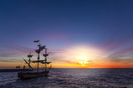 Photo pour Silhouette of a pirate ship leaving the harbor for a long campaign on the ocean chasing, pirating other marchand ship with copy space - image libre de droit