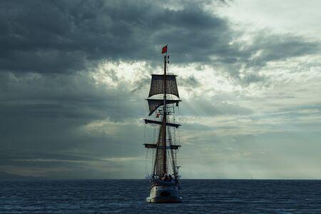 Photo pour Antique tall ship, vessel leaving the harbor of The Hague, Scheveningen under a warm sunset and golden sky - image libre de droit