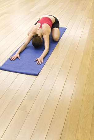 The girl is engaged in yoga in a hall with a wooden floor