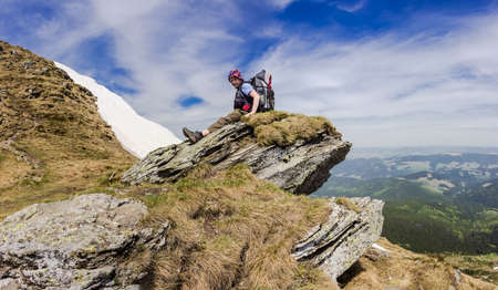 Young tourist with a backpack on a rocky ledge of the mountain ridge on a background of forested mountains, snowfields and sky. Carpathians.