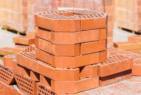Several red perforated decorative bricks with a beveled edge in warehouse closeup on a background of pallets with exactly the same bricks.