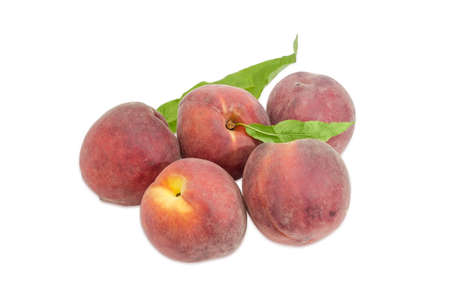 Several ripe fresh peaches with leaves on a light background
