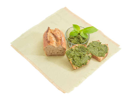 Two sandwiches with sauce pesto, part of bread and sauce basil pesto in small glass bowl decorated with green basil twig on a napkin on a white background