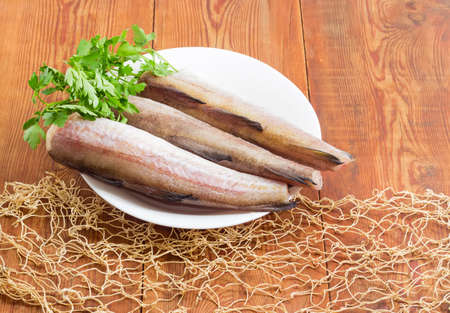 Uncooked carcasses of the Alaska pollock without of head and tail and bundle of parsley on a white dish on a surface of old wooden planks with fishing net