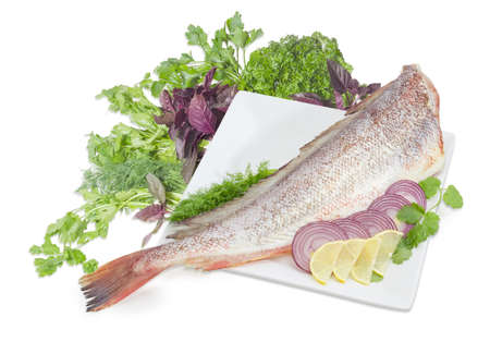 Carcass of the uncooked red cod without head, sliced lemon and red onion on the large square white dish, cilantro, basil, parsley and dill twigs on a white background