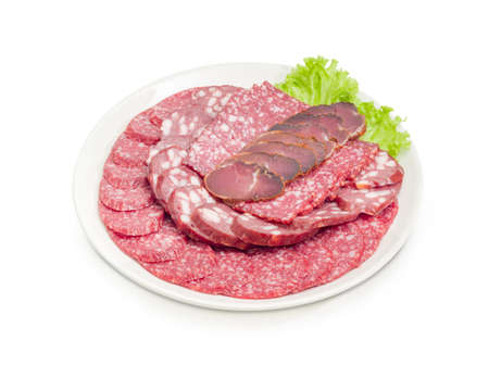 Sliced two different salami, smoked sausage and dried pork tenderloin on lettuce leaf on the white dish on a white background