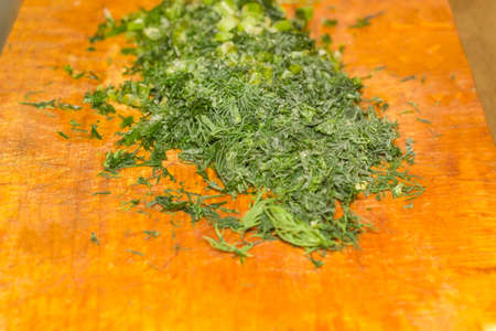 Fragment of the wooden cutting board with chopped frozen dill covered with rime at selective focus