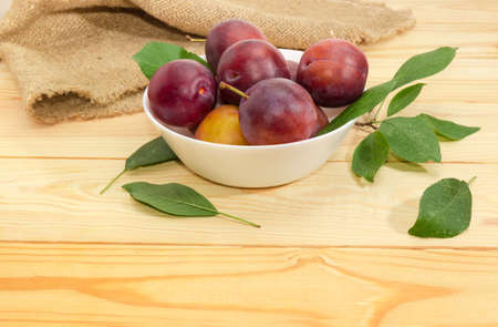 Ripe purple plums in white bowl and leaves of plum tree at selective focus on a light colored wooden surface