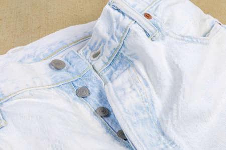 Photo pour Upper part of the new light colored artificially aged jeans, fragment close-up - image libre de droit