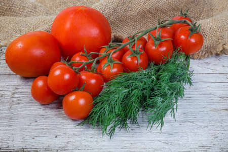 Foto für Cluster of the fresh ripe red cherry tomatoes, two ordinary tomatoes and bundle of dill on the old cracked wooden surface with burlap - Lizenzfreies Bild