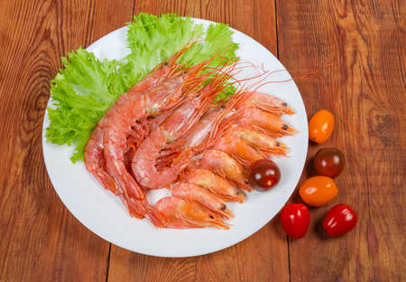 Photo pour Argentinian red shrimps and usual shrimps with fresh lettuce leaves on dish and varicolored tomatoes cherry on the wooden rustic table - image libre de droit