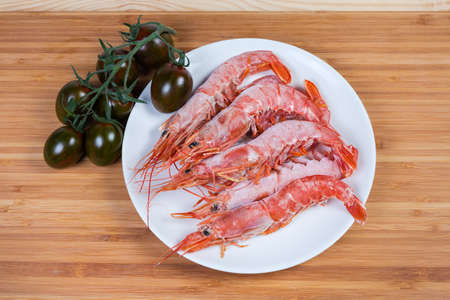 Photo pour One frozen ocean king prawn and several usual shrimps on dish, cluster of the fresh cherry tomato kumato on a wooden surface, top view - image libre de droit