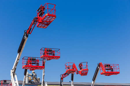 Photo for Red baskets on the white booms of different articulated boom lifts and top parts of lifts on a background of clear sky - Royalty Free Image
