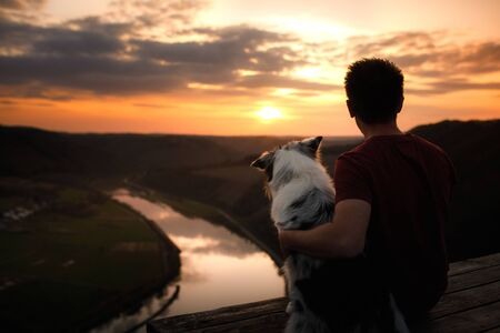 Photo pour A man with a dog at sunset. walk with a pet. Australian Shepherd and owner in nature look at a beautiful view  - image libre de droit