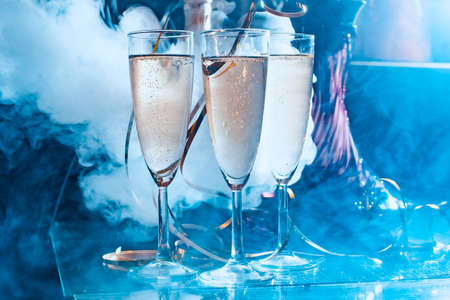 Recreation and holiday celebration concept. Toned image. Many glasses filled with champagne or white wine next to a hookah view close