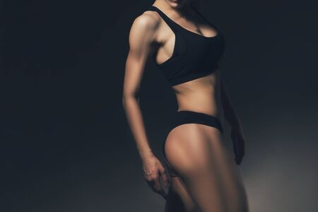 Photo for Sexy slim fit woman body. Muscled back. Sportswear. Dark background - Royalty Free Image