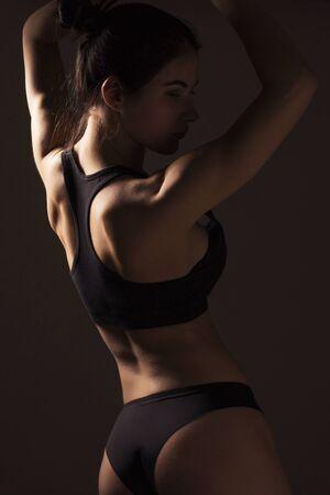 Photo pour Sexy slim fit woman body. Muscled back. Sportswear. Dark background - image libre de droit