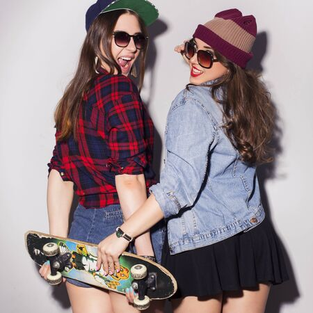 Photo for Two beautiful brunette women (girls) teenagers spend time together having fun, make funny faces. Casual hipster outfit, jeans jacket and plaid shirt, with a skateboard - Royalty Free Image