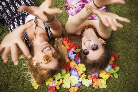 Photo pour Two young beautiful blonde hipster girls on summer day having fun in european city. Green grass on a background and flower leafs. Copy space - image libre de droit