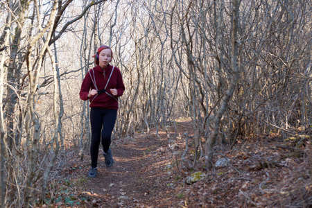 Photo pour teenage girl in headphones runs along a forest trail with a backpack. - image libre de droit