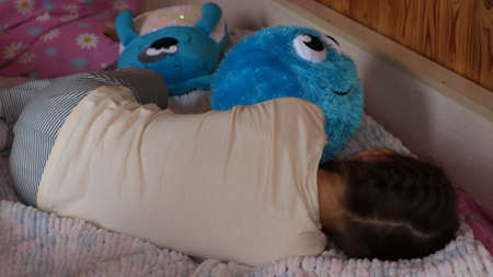Photo for a girl from the back lies on a pink bed next to blue soft toys that contains various emotions - Royalty Free Image