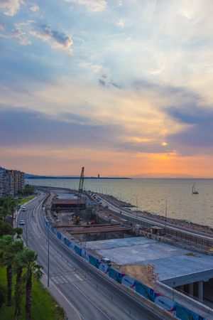 IZMIR, TURKEY – AUGUST  3, 2017: The process of building an underground tunnel on the road on the Aegean Sea in the Konak area of Izmir Turkey the view during sunset with a yacht floating on the sea toned image